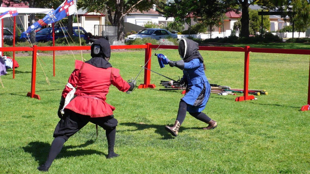 Her Majesty Angharat fencing with offhand parrying Captain Innilgard action figure. Photo by Baroness Ingerith Ryzka, April 2014