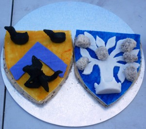 Sotelties made of Carys Brede (shortbread with caraway seeds), topped by sugarplate, of Baron Drake Morgan and Baroness Blodeuwedd y Gath's heraldry,  with elements completed in leche lumbard rolled in almond meal. Made by Baroness Blodeuwedd y Gath. Photo by Lady Ursula Von Memmingen, April 2014