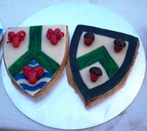 Sotelties of macaroon cooked in the shape of a shield, and marzipan, rolled flat and painted, with elements of Baron Osgot of Corfe and Baroness Esla of Ifeld 's heraldry done in three dimensions. Made by Baroness Blodeuwedd y Gath. Photo by Lady Ursula Von Memmingen, April 2014