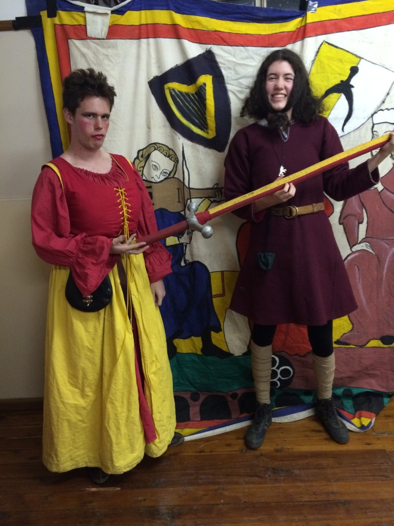 The seneschal of St Andonicus handing the Sword of Knowledge to the seneschal of St Ursula. Photo by TH Lady Ceara Shionnach, July 2014
