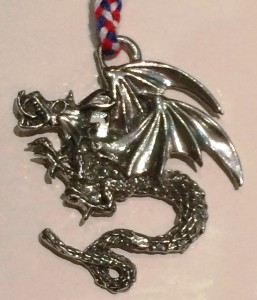The token for the Red Wyvern is a silver pendant depicting a basilisk, photo by Ceara Shionnach.