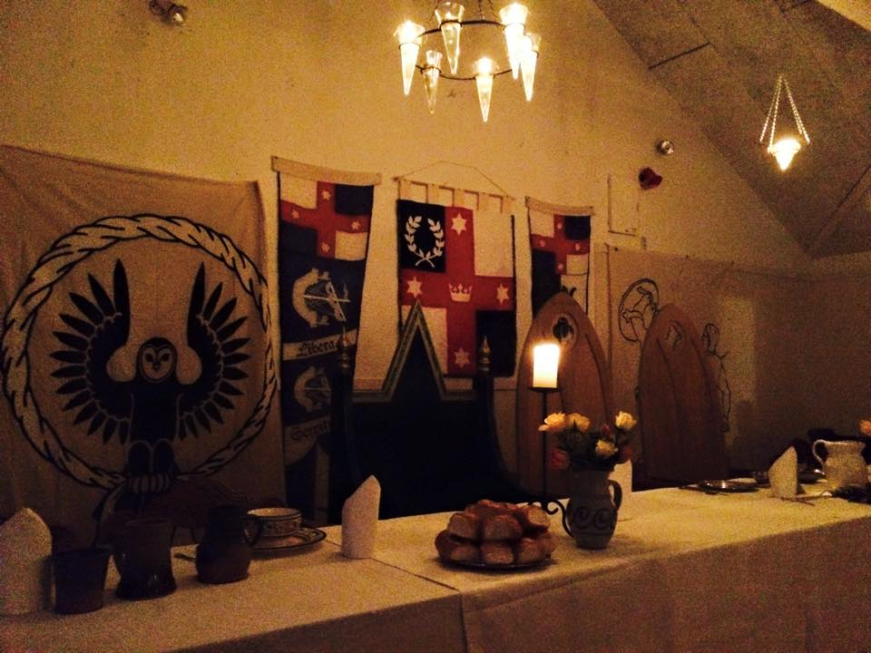 High Table illuminated at the feast by suspended oil lights. Photo by THL Ceara Shionnach, May 2015.