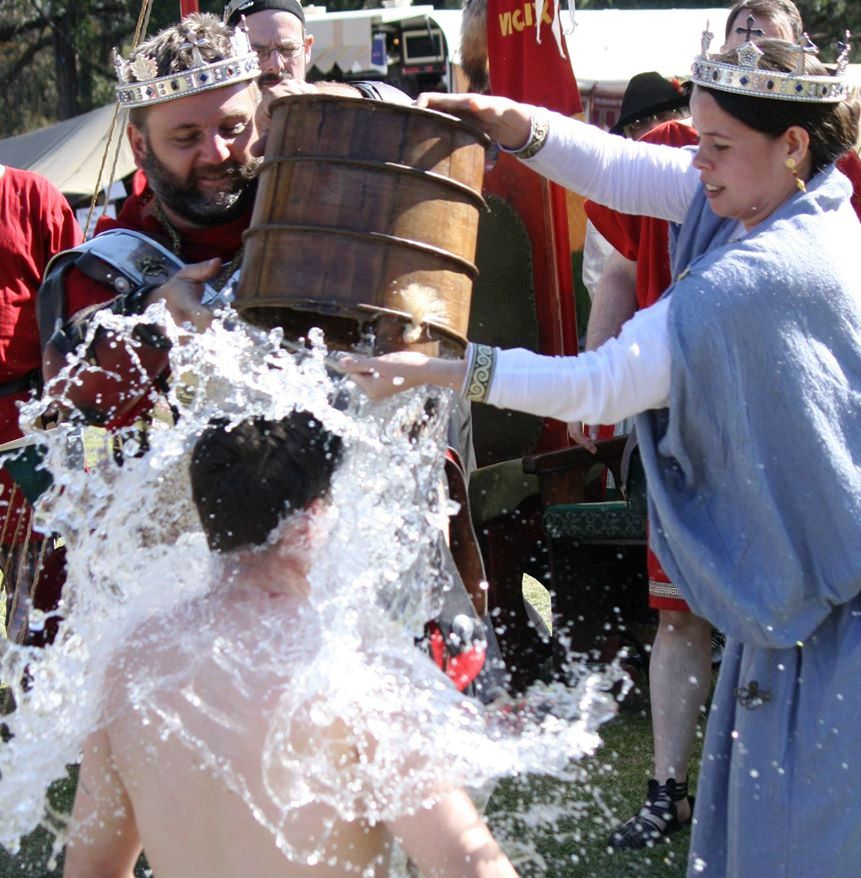 In an Atlantian tradition, Lucas was doused with a bucket of water by the Crown during his Knighting ceremony. Due to comments he'd previously made, the bucket of water had ice and a bottle of rose water added to it. Photo by Duchess Constanzia Moralez y de Zamora.
