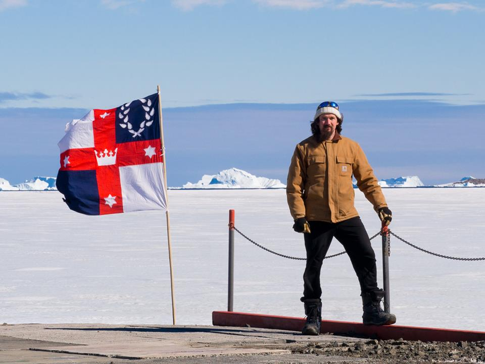 Lochacian Bob the Cold with a Lochac flag at Davis Station in Antarctica, displayed in response to Caid's attempt to claim the southern continent for themselves. Photo by Bob the Cold, November 2014.