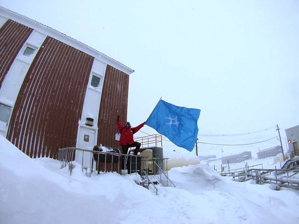 Lord Sigvaldr Bjarnarsen displaying the arms of the Kingdom of Caid at McMurdo Station in Antarctica, attempting to claim Lochacian lands. Photo posted by Lord Sigvaldr Bjarnarsen, 9 October 2014.
